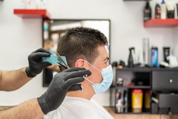 Man getting hair cut at the barbershop wearing mask. Premium Photo