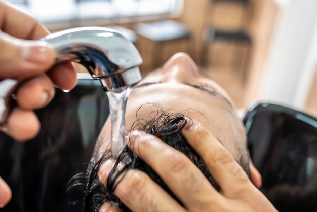 Man getting a hair washed in barber shop. Premium Photo