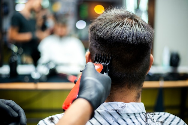 Man getting a haircut with blurred mirror reflection Free Photo