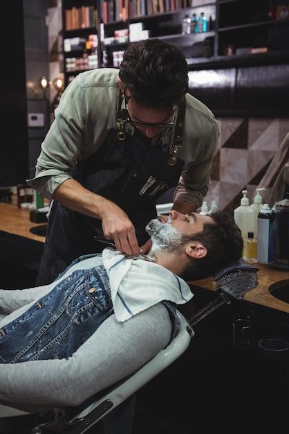 면도기로 면도 한 그의 수염을 얻는 남자 무료 사진