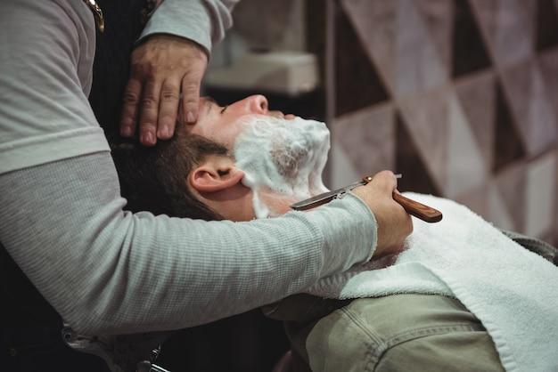 Uomo che ottiene la sua barba rasata con il rasoio Foto Gratuite