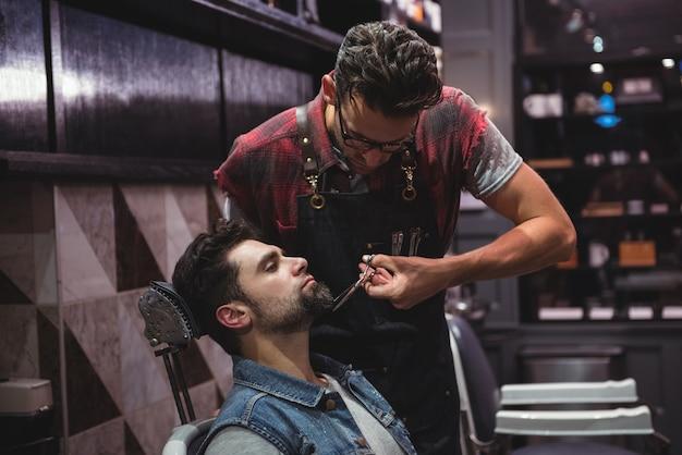 Мужчина подстригает бороду ножницами Бесплатные Фотографии