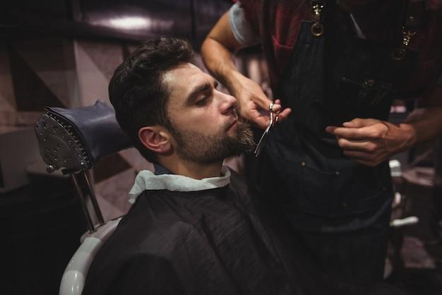 はさみで髭を整える男 無料写真