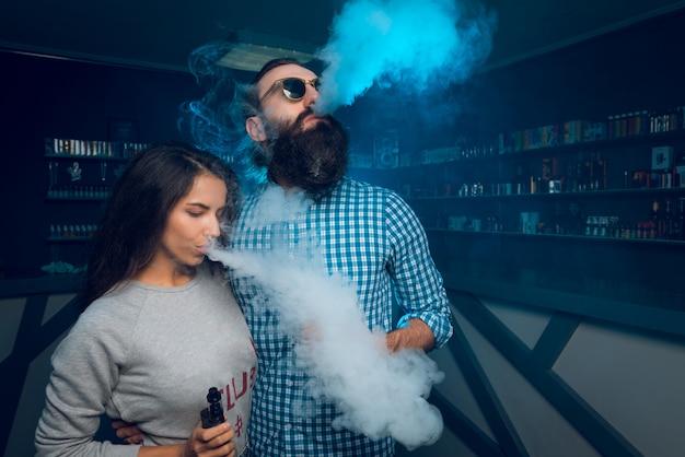 A man and a girl smoke a cigarette and release smoke. Premium Photo