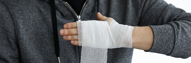 Man give himself first aid rolling bandage tape over wrist close-up Premium Photo
