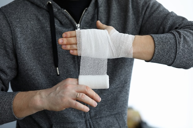 Man give himself first aid rolling bandage tape over wrist Premium Photo