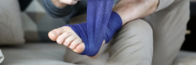 Man give himself first aid rolling blue bandage tape over foot close-up Premium Photo