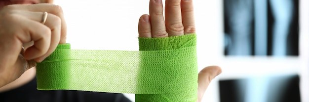 Man give himself first aid rolling green bandage tape over wrist close-up Premium Photo