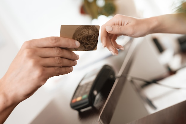 A man gives a woman a bank card for payment. Premium Photo