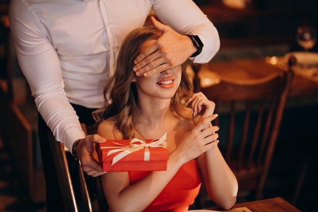 Человек, давая подарочной коробке на день святого валентина в ресторане Бесплатные Фотографии