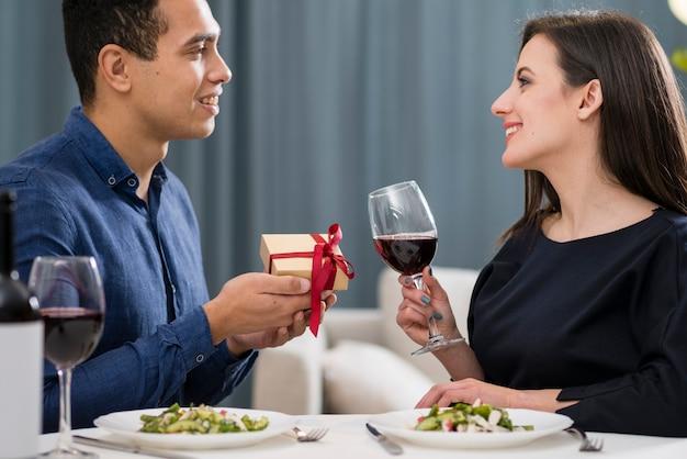Мужчина дарит подарок своей девушке на день святого валентина Premium Фотографии
