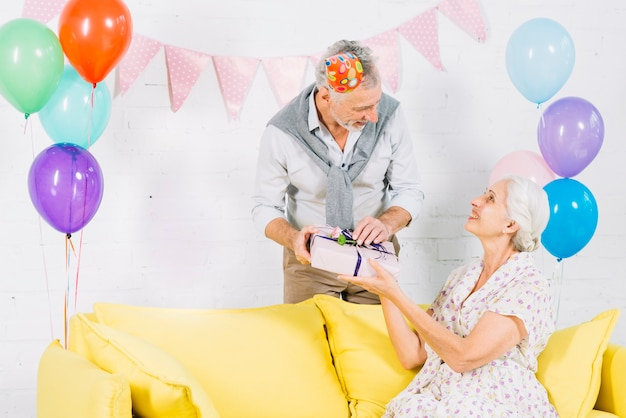 Man giving birthday gift to his wife sitting on sofa Free Photo