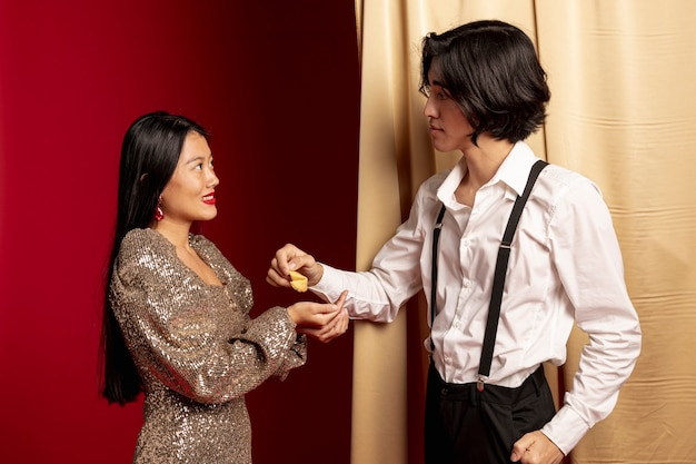 Man giving fortune cookie to woman for chinese new year Free Photo