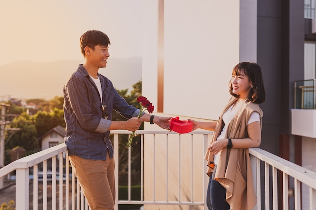 Man giving his girlfriend a heart-shaped box and a rose Free Photo