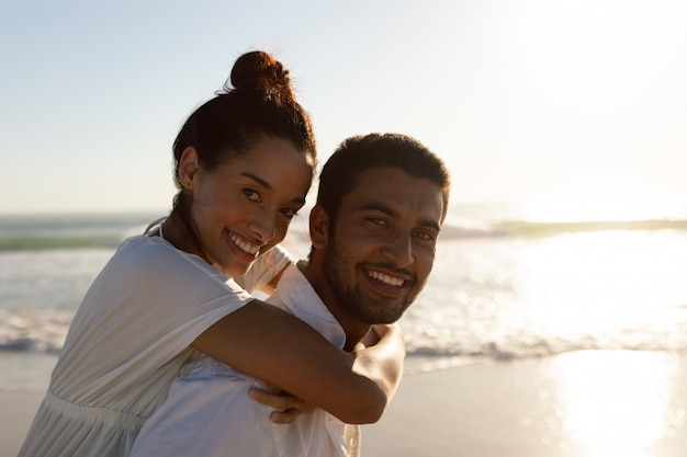 Man giving piggyback ride to woman on the beach Free Photo