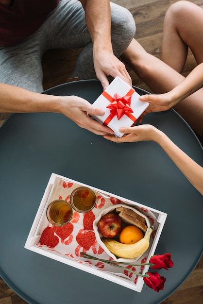 Man giving small gift box to woman Free Photo