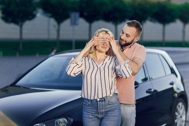 새 차를 구입하여 여자에게 놀라움을주는 남자. 젊은 부부는 차를 구입하고 남자와 여자는 거리의 차 근처에 서 있습니다. 사랑하는 사람을위한 깜짝 선물. 프리미엄 사진