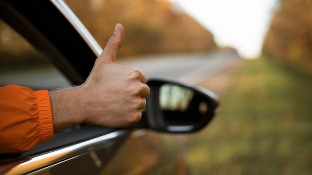 Mężczyzna wyciągający kciuki z samochodu podczas podróży Darmowe Zdjęcia