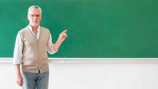 Man in glasses pointing at blackboard Free Photo