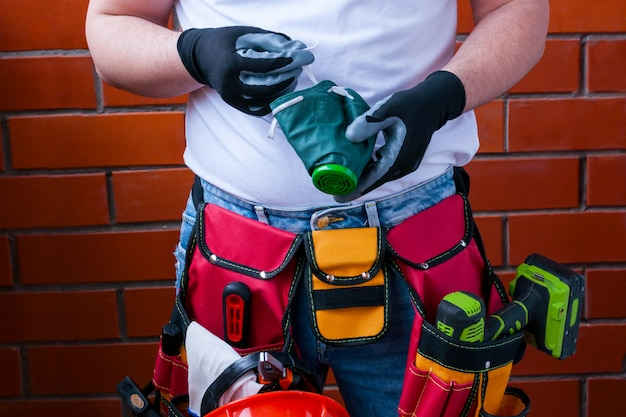 A man in gloves with a respirator against the background of a red brick wall with a full bag for tools. Premium Photo