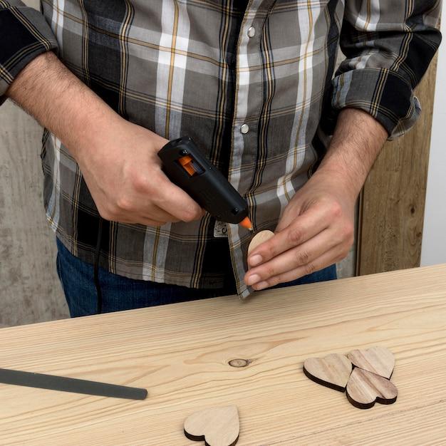 Man glueing a piece of wood Free Photo