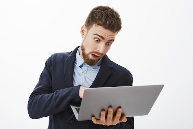 Man going crazy, being in rush working on project. anxious troubled good-looking male with beard in suit holding laptop looking at computer screen, posing concerned and focused against grey wall Free Photo