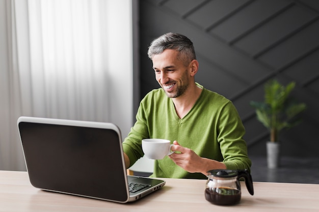 Man in green shirt smiles and using his laptop Free Photo