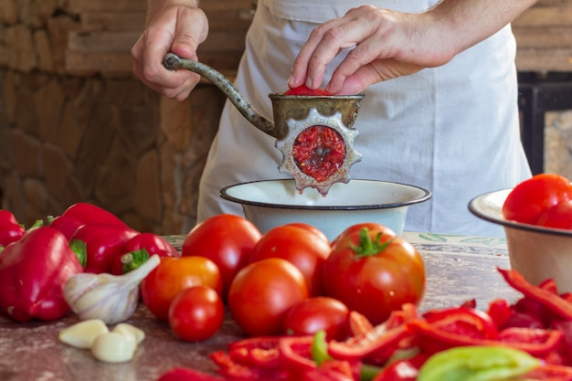 A man grinds tomatoes and bulgarian pepper in a meat grinder to make lecho sauce Premium Photo