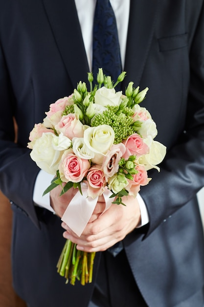 Man groom holds the bridal bouquet. guy in jacket Premium Photo