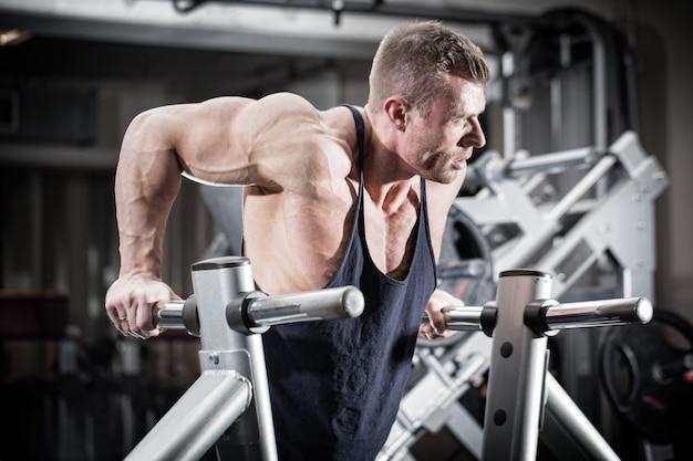 Man in gym at dip exercise Premium Photo