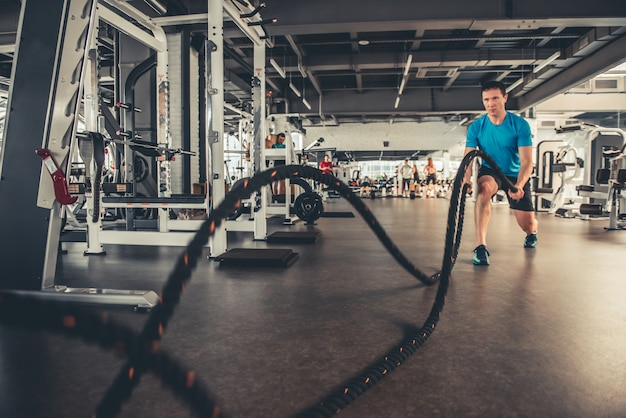 A man in the gym does exercise with a rope. Premium Photo
