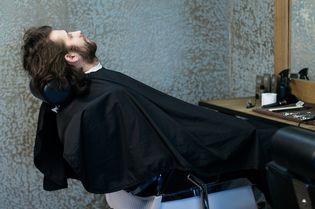 Man at the hairdressing salon sitting in the armchair, waiting for a barber Premium Photo