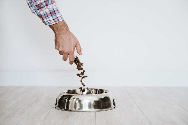 Man hand filling a bowl of dog food at home Premium Photo