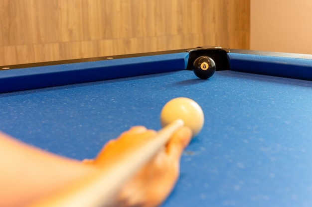 Man hand hold a billiard stick end the game. Premium Photo