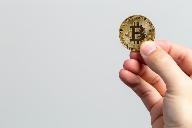 白い背景の前に物理的なビットコインを持っている男の手 Premium写真