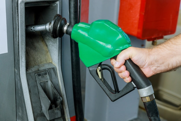Man hand holding fuel nozzle to add gas at petrol station Premium Photo
