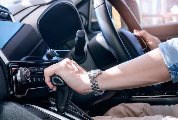 Man hand holding gear stick levels. driver man hand holding automatic transmission in car. Premium Photo