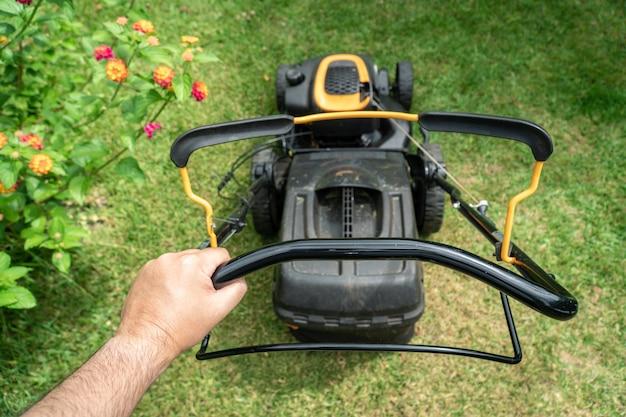 Man hand holding a lawn mower machine to cutting green grass Premium Photo