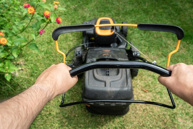 Man hand holding a lawn mower machine to cutting green grass Premium Photo