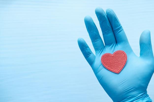 赤いハートを保持している保護手袋の男の手。 Premium写真