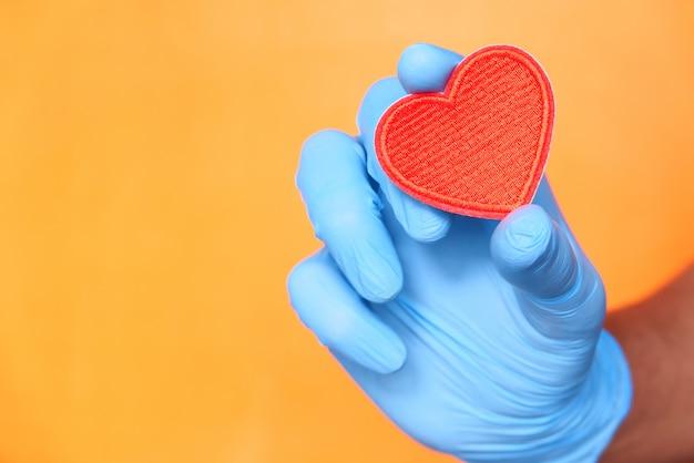 赤いハートを保持している保護手袋で男の手。 Premium写真