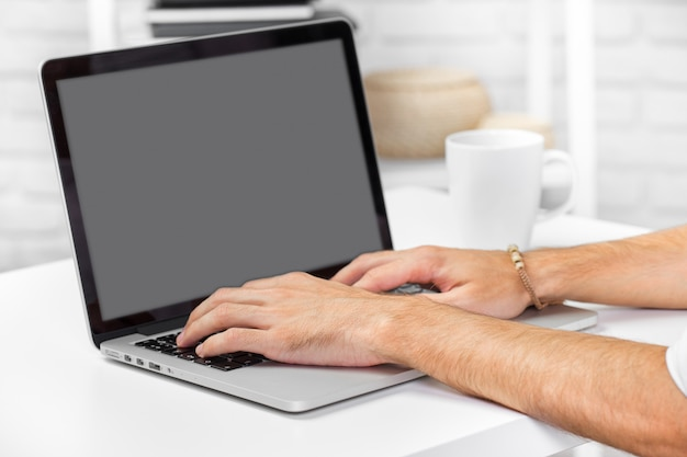 Man hand on laptop keyboard with blank screen monitor close up Premium Photo