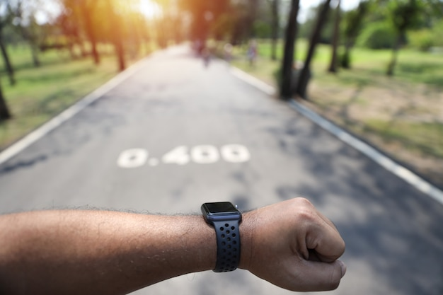 Man hand looking at smart watch while jogging in the park Premium Photo