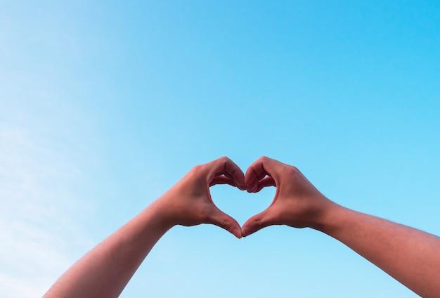 Man hand making heart form love blue sky. Premium Photo