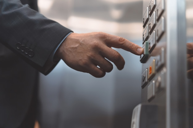 Man hand office worker in a business suit press the elevator button with his finger. businessman in Premium Photo