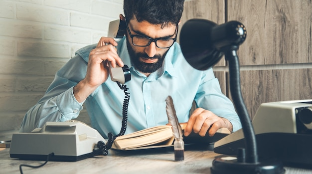 Человек рука телефон с книгой на столе Premium Фотографии