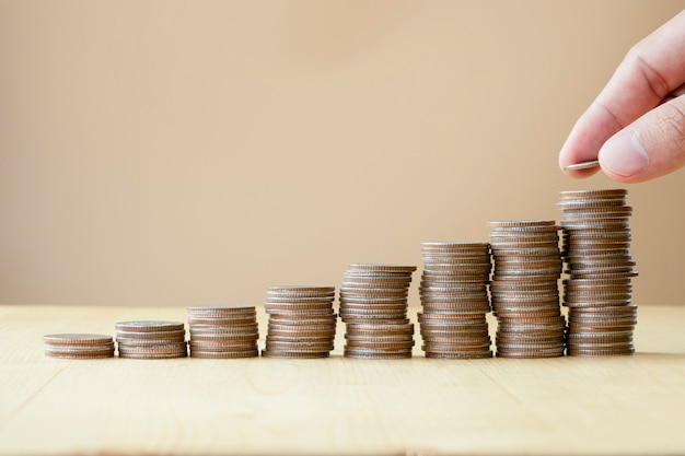 Man hand putting coins stacking for growth business and saving investment concept. Premium Photo