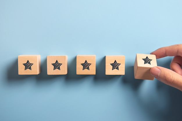 Man hand putting wooden five star shape on blue. best excellent services rating customer experience concept Premium Photo