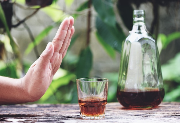 Man hand rejecting glass with alcoholic beverage on table outdoors surface refuses to drink a alcohol whiskey Premium Photo