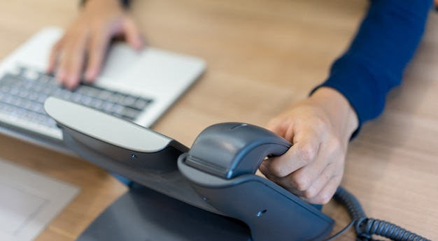 Man hand toucing on handset telephone with working on laptop Premium Photo